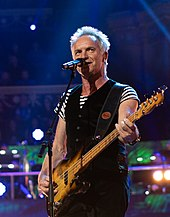 Sting playing guitar onstage.