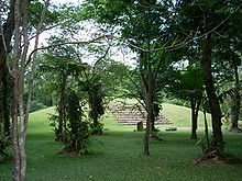 A large grassy mound seen through widely spaced trees scattered across a flat grassy foreground. A stone stairway climbs the mound and several stone monuments stand in front of this stairway. More trees form the backdrop to the mound.