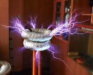 Tesla coil - Homemade Tesla coil in operation, showing brush discharges from the toroid. The high electric field causes the air around the high voltage terminal to ionize and conduct electricity, allowing electricity to leak into the air in colorful corona discharges, brush discharges and streamer arcs. Tesla coils are used for entertainment at science museums and public events, and for special effects in movies and television.