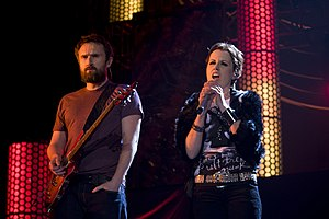 Noel Hogan holding a guitar and Dolores O'Riordan singing into a microphone