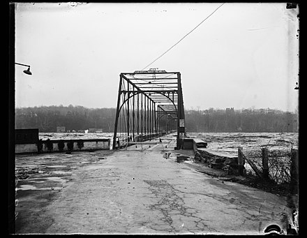 The Potomac River surges over the deck of Chain Bridge during the historic 1936 flood. The bridge was so severely damaged by the raging water, and the debris it carried, that its superstructure had to be re-built; the new bridge was opened to traffic in 1939. (This photograph was taken from a vantage point on Glebe Road in Arlington County, Virginia. The houses on the bluffs in the background are located on the Potomac Palisades of Washington, DC.) The Potomac River surges over Chain Bridge during 1936 Flood 19 March 1936.jpg