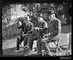 Three men, including Judge Alfred Paxton Backhouse, wearing suits and hats seated on a lawn, 1910-1939 (7737068570).jpg