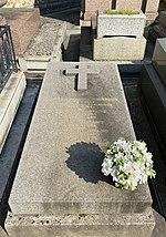 Foto van een graftombe met een kruis in reliëf op het bovenste gedeelte, een lijst met namen gegraveerd in goud in het midden en een boeket bloemen rechtsonder