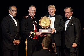 A ceremony in which Trump receiving the 2015 Marine Corps–Law Enforcement Foundation's annual Commandent's Leadership Award. Four men are standing, all wearing black suits; Trump is second from the right. The two center men (Trump and another man) are holding the award.