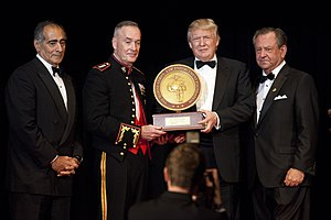 A ceremony in which Trump receiving the 2015 Marine Corps–Law Enforcement Foundation's annual Commandant's Leadership Award. Four men are standing, all wearing black suits; Trump is second from the right. The two center men (Trump and another man) are holding the award.