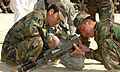Two Afghan National Army recruits adjust a weapon during a weapons qualifying course (4438145846).jpg