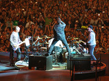 U2 performs on a stage. Bono stands in the center facing away towards a drum kit, with each leg on an amplifier. The Edge, playing guitar to his right, faces him. Adam Clayton, playing bass to his Bono's left, faces him. Fans are visible in the background