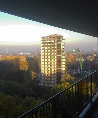 Long reach excavator - UHD demolishing a high-rise building