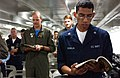 US Navy 030727-N-8148A-109 Petty Officer 3rd Class Thomas Padilla from Weslaco, Texas, sings the Processional hymn during the end of first underway Roman Catholic Mass aboard the newly commissioned nuclear powered aircraft carr.jpg