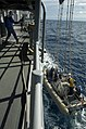 US Navy 050622-N-5781F-024 Deck department Sailors assigned to the guided missile cruiser USS Cowpens (CG 63) tend lines while retrieving a rigid hull inflatable boat (RHIB) after conducting small boat exercises.jpg