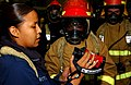 US Navy 050713-N-6125G-004 Damage Controlman 3rd Class Louchelle Loretto, left, trains a fire party on how to use the new Naval Firefighting Thermal Imager (NFTI) during a general quarters drill.jpg