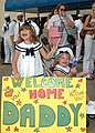 US Navy 070702-N-1522S-004 Two young girls anxiously cheer for their father, Gas Turbine System Technician (Mechanical) 1st Class David Pfister, during the homecoming of guided-missile frigate USS Underwood (FFG 36).jpg