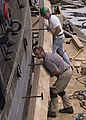 US Navy 090513-N-1060K-122 Ship restorers Chris Hanlon, bottom, and Paul Chiasson line up a new plank of white oak along USS Constitution's starboard side.jpg