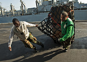 US Navy 120105-N-BT887-589 Yeoman 3rd Class Jaren Cleveland and Logistics Specialist Seaman Luis Colon pull cargo aboard the Nimitz-class aircraft.jpg