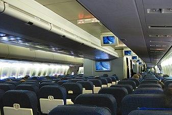 Cabine principal da aeronave com dois corredores e várias fileiras de assentos.