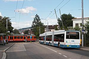 Zürich Friesenberg railway station - Uetliberg train and city bi-articulated trolleybus cross at Friesenberg station