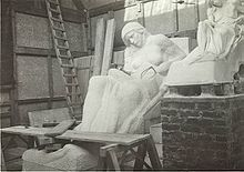 The partially completed statue of a reclined woman sits to the right of a half sized model of the same statue. It appears the work is being conducted inside a temporary structure.