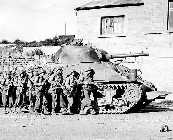 Combined arms in action: US M4 Sherman, equipped with a 75 mm main gun, with infantry walking alongside. Yanks advance into a Belgian town.jpg