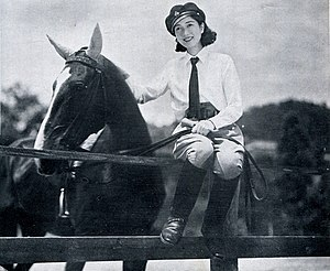 Yukiko sits on a fence with one arm around a horse