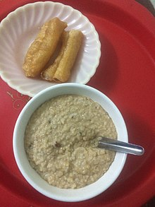 Thick, brown, medium textured porridge in bowl next to plate of fried tofu.