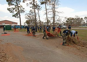 International response to Hurricane Katrina - Mexican marines and U.S. Navy sailors cleaning up hurricane debris outside of a Mississippian elementary school.