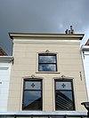 foto van Huis met derde kwart 19e-eeuwse gepleisterde lijstgevel. Moderne winkelpui