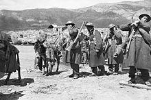 Eine Gruppe von Mannern in Militaruniformen, darunter Stahlhelme und gro?e Trenchcoats, stand vor einer bergigen Landschaft