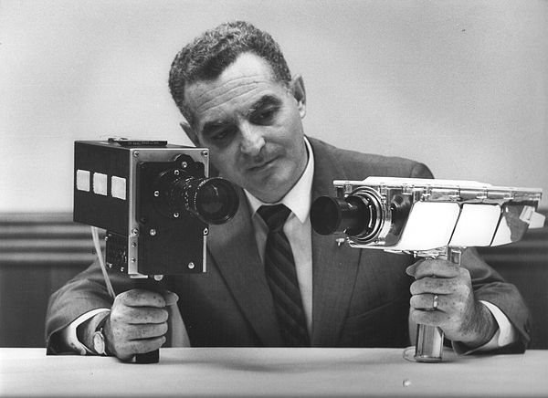 1969. Stan Lebar, the project manager for Westinghouse's Apollo Television Cameras, shows the Field-Sequential Color Camera on the left, and the Monochrome Lunar Surface Camera on the right. The Color camera was used on all flights starting with Apollo 10, while the monochrome Lunar Surface Camera was used on Apollo 11, and captured Neil Armstrong's first steps on the Moon.