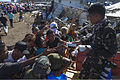 A Philippine Air Force Photographer hands out packs of biscuits to Filipinos while they wait to be manifested for air transport to Manila at the Tacloban Air Field, Philippines, Nov. 15, 2013 131115-M-UY543-181.jpg