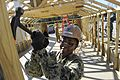 A Seabee removes nails as a hut is taken down. (8516135490).jpg