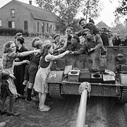 A carrier crew of 8th Rifle Brigade hands out chocolate to Dutch civilians during the advance of 11th Armoured Division in Holland, 22 September 1944. B10245