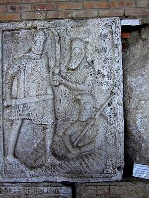 Suebian knot - A battle scene from Tropaeum Traiani: a Roman legionnaire battles a Dacian warrior wielding a falx, while a Buri warrior sporting a Suebian knot lies injured on the ground.
