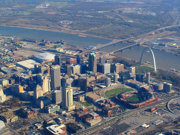 An aerial view of many skyscrapers and other buildings, with a dark blue river cutting down through the upper half.