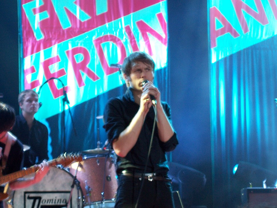 Two-thirds body shot of singer with short brown hair, wearing a black shirt and jeans, performing on stage. A band is partially visible in the background.