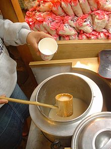 A man with a ladle pouring rice milk