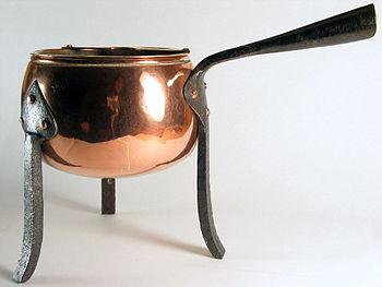 English: Ancient copper pot on three iron feet...