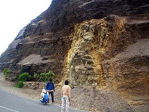 Cross-cutting relationships - Cross-cutting relationships involving an andesitic dike in Peru that cuts across the lower sedimentary strata. Both the dike and the lower strata are cut by an unconformity