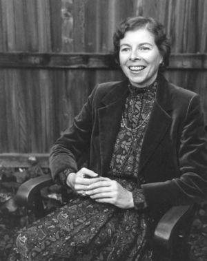 Portrait of woman with short, wavy hair, wearing an oversized velvet blazer over a floral dress