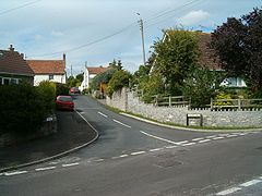 Street scene showing road junction with houses and cars