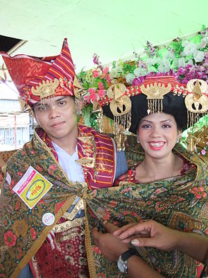Karo people (Indonesia) - Karo married couple being bound in a sling (traditionally used in Indonesia for carrying babies), wearing traditional costume including ulos (Karonese: uis) this action signifies this couple is now united as man and wife.