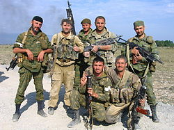 Seven soldiers in battle fatigues, with weapons