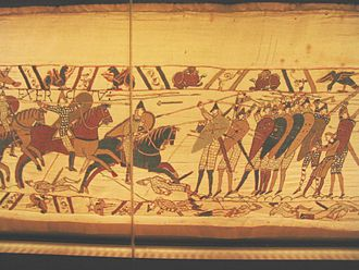 Weaponry in Anglo-Saxon England - The Bayeux Tapestry's depiction of Norman cavalry charging an Anglo-Saxon shield wall during the Battle of Hastings in 1066.