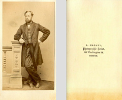 Bearded man standing by S Masury of Boston.png