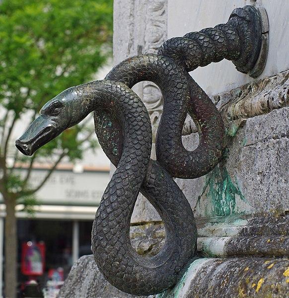 La colonne-fontaine Jeanne de Laval.  La colonne est inaugurée le 22 mai 1842.  La statue de Jeanne de Laval initialement en bronze a été déposée et emmenée par l'armée allemande en 1942. Elle a été remplacée par une statue en pierre en 1950. Les bouches de la fontaine, en bronze, en forme de serpent, sont restées.  The column-fountain Jeanne de Laval.  The column was inaugurated May 22, 1842. The statue of Jeanne de Laval initially bronze was filed and led by the German army in 1942. It was replaced by a stone statue in 1950. The mouths of the fountain, bronze snake-shaped, have remained.