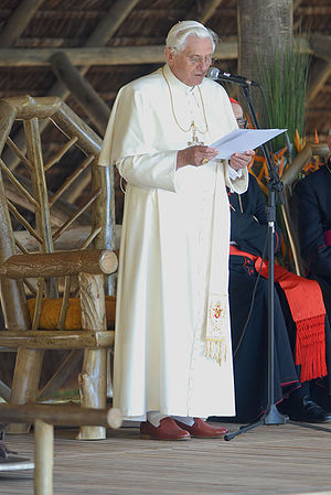 Papal regalia and insignia - Pope Benedict XVI in ordinary dress (red papal shoes, white cassock with matching pellegrina and with white fringed fascia, pectoral cross, and white zucchetto).