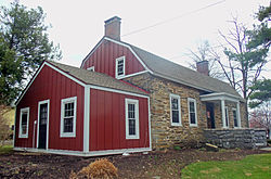 A small one-and-a-half-story stone building with a gambrel roof and one-story gabled wing on its left side photographed at an angle so that side is closer to the camera. Two chimneys rise from the roof; the wing and the roof apex on the side facing the camera are faced in vertical red boards.