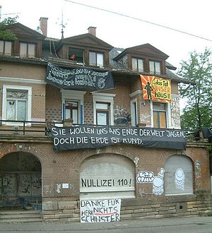 "Rauch-Haus-Song - Occupied building hung with a banner bearing the slogan ""...das ist UNSER haus"" (""... this is OUR house"") (right above)"