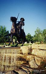 A color photograph of the Buffalo Soldier Monument at Fort Leavenworth, Kansas. The sculpture was undertaken by Eddie Dixon and sits atop a waterfall. It consists of a cavalry trooper mounted on a galloping horse