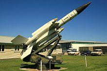 Photo shows a white surface-to-air missile in a museum setting.
