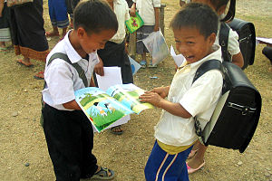 English: Two boys in Laos laugh over the book ...